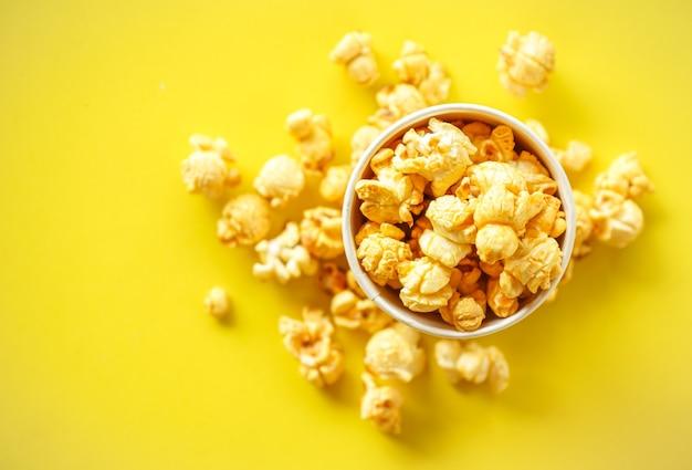 Widok z góry popcornu w papierowym szkle na żółtym tle z miejscem na kopię