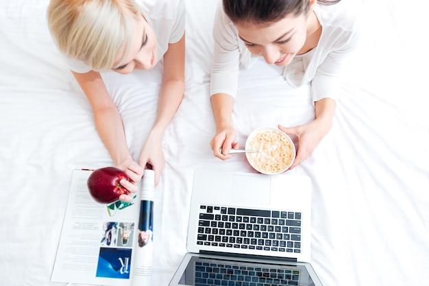Widok z góry portret dwóch kobiet leżących na łóżku i korzystających z laptopa