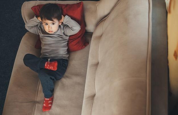 Widok z góry portret kaukaski chłopca na białym tle w domu podczas kwarantanny, leżąc na kanapie