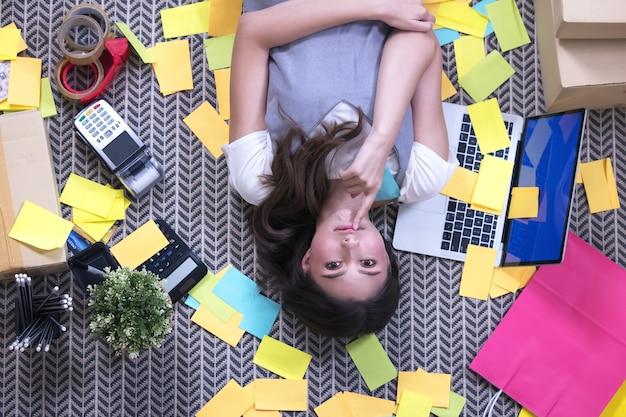 Widok z góry portret kreatywnej młodej kobiety leżącej z zamkniętymi oczami w rozrzuconych po całym świecie dziełach sztuki i wzornictwie
