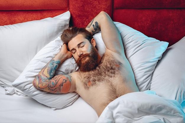 Widok z góry portret śpiącego pięknego mężczyzny węchowego z wąsem brodą i tatuażem, leżącego na plecach na białym łóżku i śpiącego.