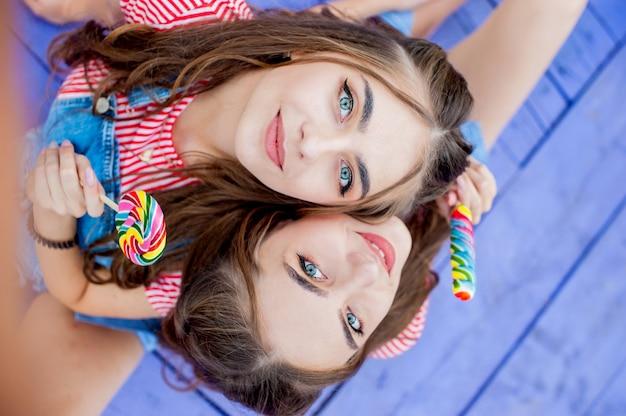 Widok z góry portretowych sióstr bliźniaczek w kolorowych ubraniach z lizakami, siedzących na fioletowych deskach