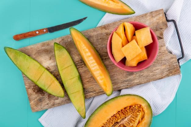 Widok z góry posiekane plasterki melona kantalupa na drewnianej desce kuchennej z nożem na niebiesko