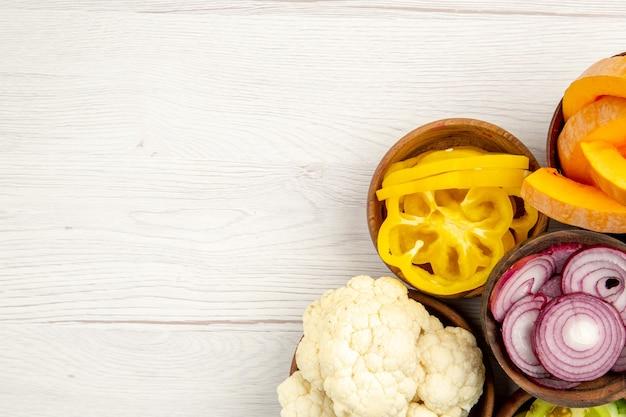 Widok z góry posiekane warzywa pokrój dyni pokrój żółtą paprykę pokrój cebulę kalafior w miseczkach na białym stole wolne miejsce