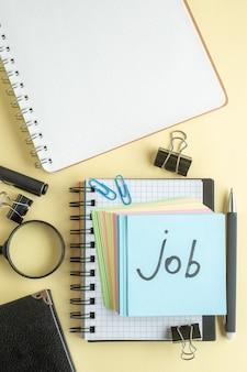 Widok z góry praca pisemna notatka wraz z kolorowymi niewielkimi papierowymi notatkami na jasnym tle notatnik pióro biuro szkolne zeszyt praca biznes pieniądze kolor pracy
