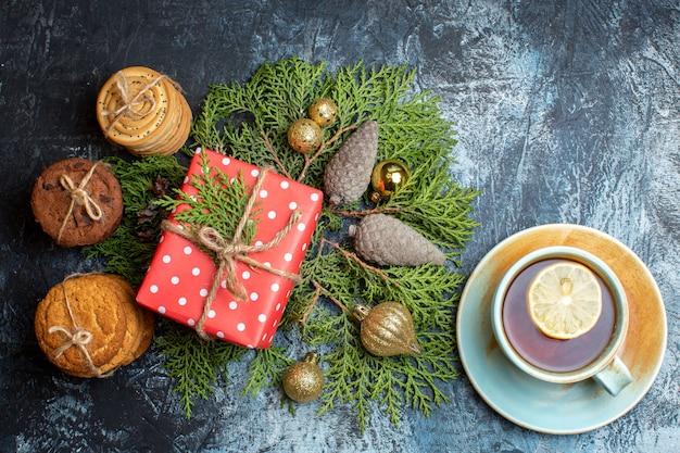 Widok z góry prezent świąteczny z różnymi ciastkami i filiżanką herbaty
