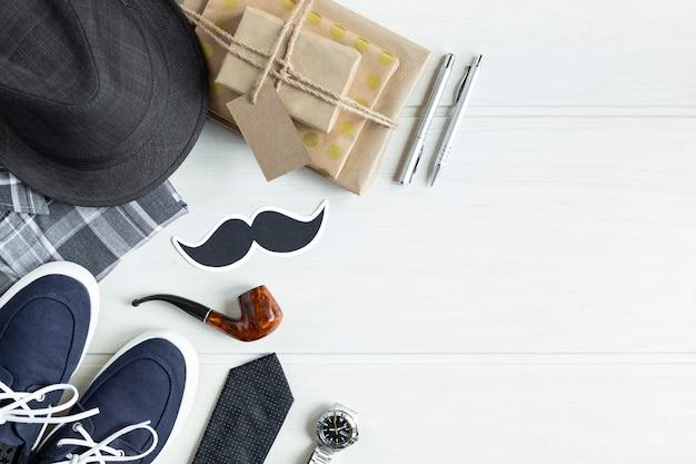 Widok z góry prezentów i innych męskich akcesoriów odzieżowych na białym drewnianym