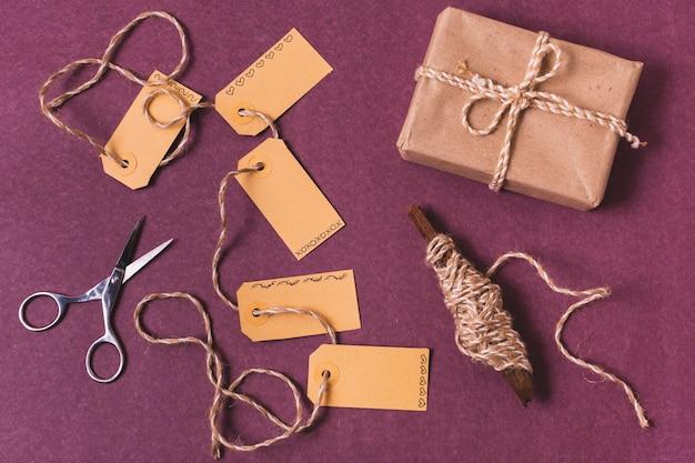 Widok z góry prezentu z tagami i nożyczkami