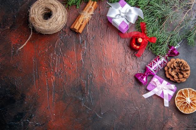 Widok z góry prezenty świąteczne gałąź drzewa ze stożkiem zabawki choinkowe nić ze słomy cynamonowej na ciemnoczerwonej powierzchni