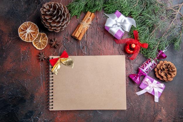 Widok z góry prezenty świąteczne gałęzie sosny ze stożkiem zabawki choinkowe cynamon suszone plasterki cytryny anyż notatnik na ciemnoczerwonej powierzchni
