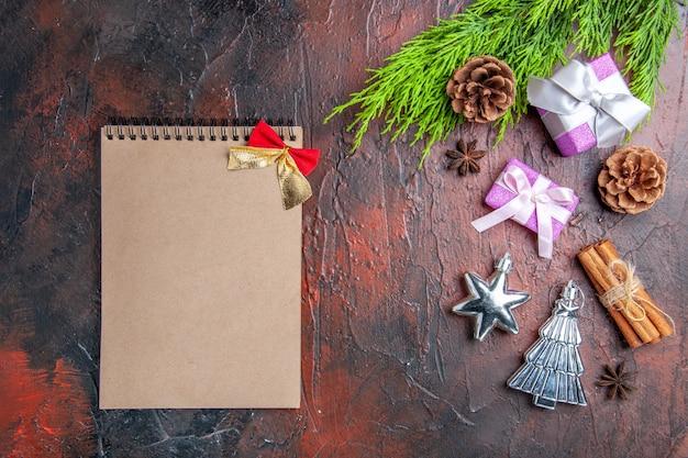Widok z góry prezenty świąteczne z różowymi pudełkami i białą wstążką gałęzie drzew anyż cynamonowe zabawki choinkowe notatnik na ciemnoczerwonym tle