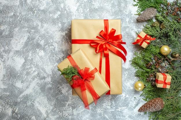 Widok z góry prezenty świąteczne zapakowane w czerwone kokardki i drzewo na białym świątecznym kolorze świątecznym prezentem fotograficznym nowy rok