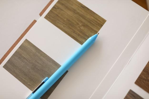 Widok z góry próbek materiałów. pokrycie podłogi lub ściany. niebieski długopis na pulpicie. profesjonalna agencja projektowania wnętrz. rzeczy robocze na stole.