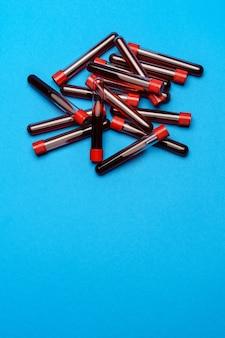 Widok z góry probówek medycyny z próbkami krwi na niebieskim tle.