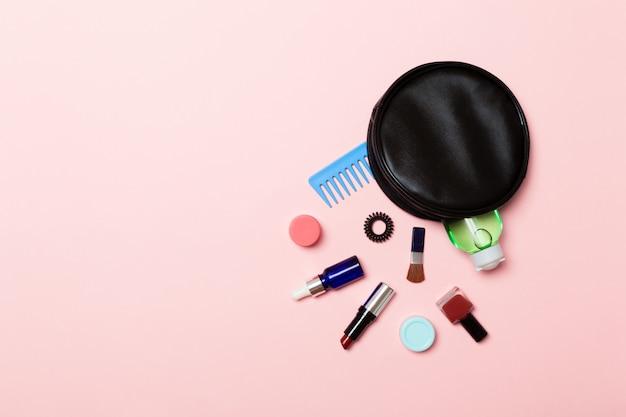 Widok z góry produktów do makijażu wypadł z torby kosmetyczne na różowym tle
