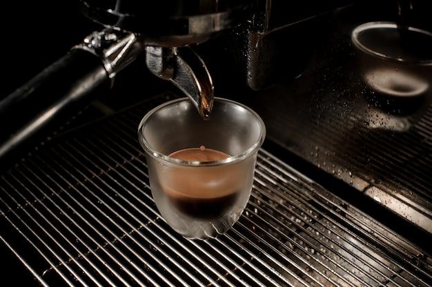 Widok z góry profesjonalnego nowoczesnego ekspresu do kawy wlewając świeżą i aromatyczną kawę do filiżanki
