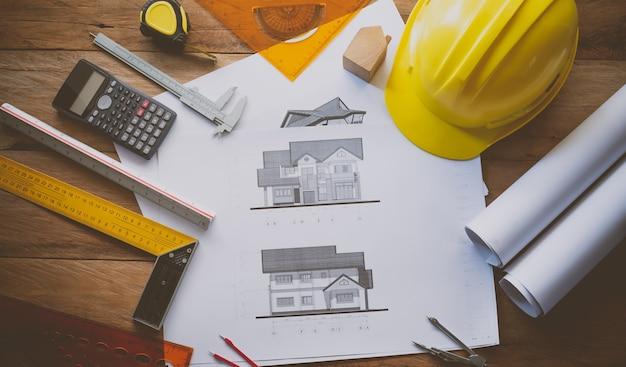 Widok z góry projekt domu i sprzęt roboczy składający się z kalkulatora, kompasu, kompasu, kasku, umieszczony na drewnianej podłodze. wyposażenie koncepcyjne pracujących inżynierów,