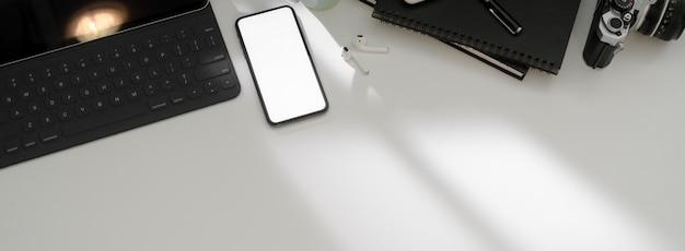 Widok z góry prostego obszaru roboczego ze smartfonem, tabletem, dodatkami biurowymi i kopią pustego ekranu