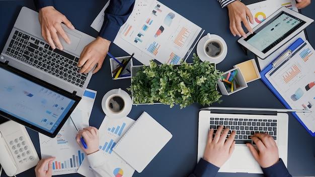 Widok z góry przedsiębiorców analizujących wykresy firmy, dokumenty opracowujące strategię finansową