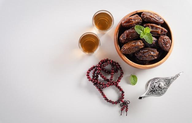 Widok z góry przedstawiający dekorację ramadan kareem, daktyle, lampkę aladyn i różaniec