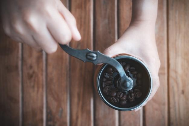 Widok z góry przedstawiający dłonie kobiety za pomocą drewnianego młynka do kawy do mielenia ziaren kawy