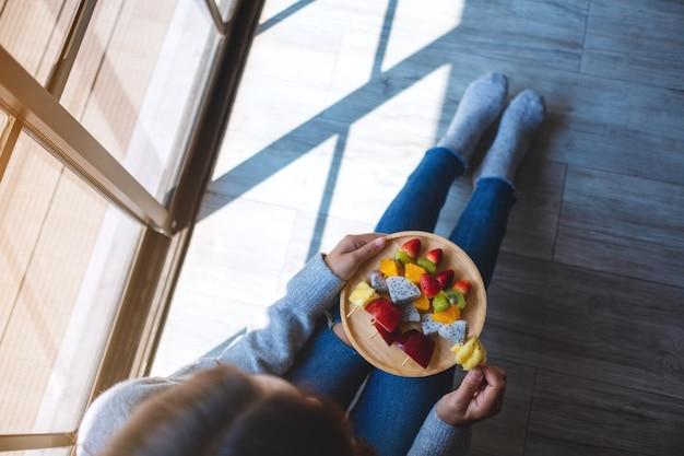 Widok z góry przedstawiający kobietę jedzącą i trzymającą drewniany talerz świeżych mieszanych owoców na szaszłykach, siedząc na podłodze