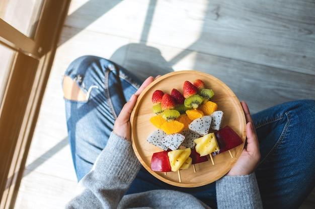 Widok z góry przedstawiający kobietę siedzącą na podłodze trzymającą drewniany talerz świeżych mieszanych owoców na szaszłykach