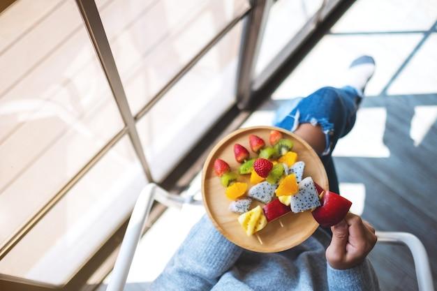 Widok z góry przedstawiający kobietę trzymającą drewniany talerz świeżych mieszanych owoców na szaszłykach
