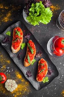 Widok z góry przekąska z sałatką pomidorową i krojonym chlebem i rukolą w ciemnym talerzu