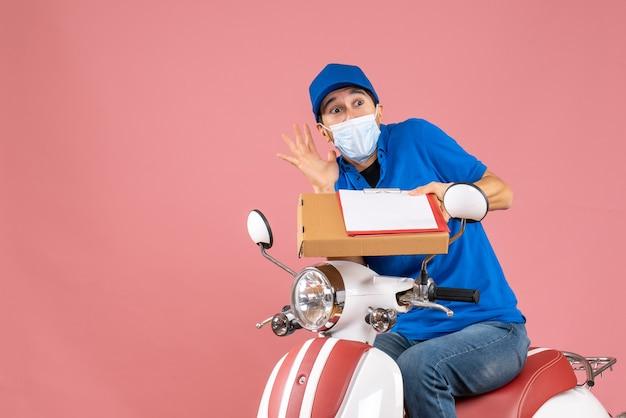 Widok z góry przestraszonej męskiej dostawy w masce w kapeluszu siedzącej na skuterze dostarczającej zamówienia trzymające dokument na brzoskwiniowym tle