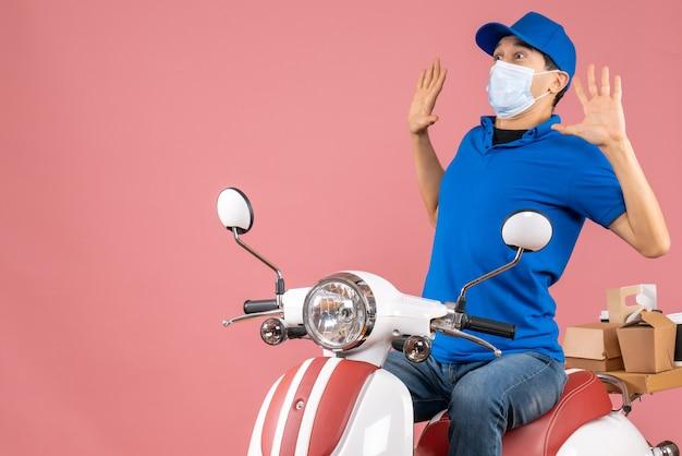 Widok z góry przestraszony facet dostawy w masce medycznej w kapeluszu siedzi na skuterze na pastelowym brzoskwiniowym tle