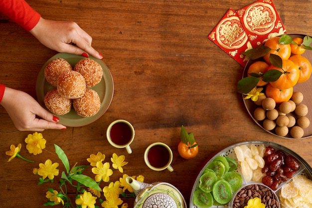 Widok z góry przycięte ręce kobiet obsługujących dania przygotowujące do świętowania nowego roku