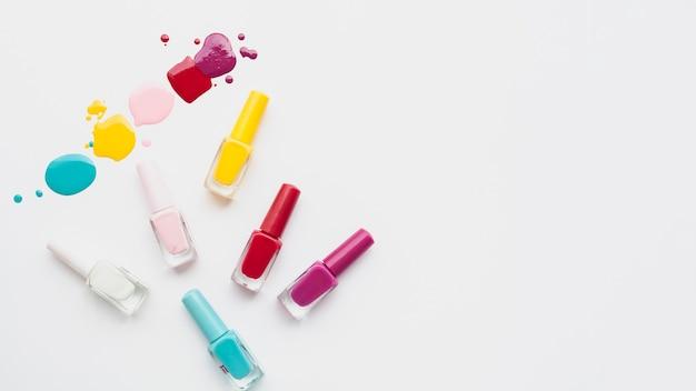 Widok z góry przygotowania z kolorowy lakier do paznokci i białe tło