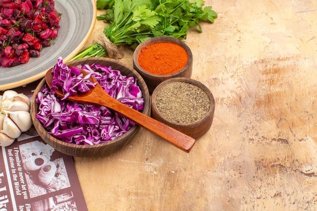 Widok z góry przygotuj miskę posiekanej czerwonej kapusty razem z pęczkiem pietruszki czosnkowej miska czarnego pieprzu kurkuma mielony pieprz do sałatki z buraków na drewnianym stole z miejscem do kopiowania