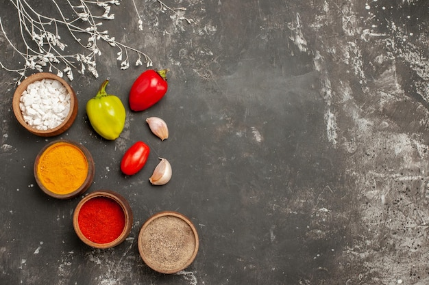 Widok z góry przypraw miski kolorowych przypraw pomidory czosnek i pieprz na ciemnym stole