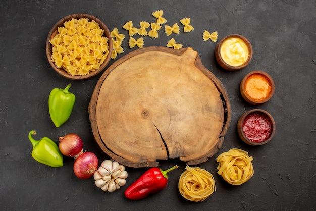 Widok z góry przyprawy makaron w misce trzy rodzaje sosu czosnek cebula czerwona i zielona papryka obok drewnianej deski do krojenia