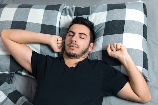 Widok z góry przystojnego mężczyzny ziewa i przeciera oczy podczas snu w łóżku.