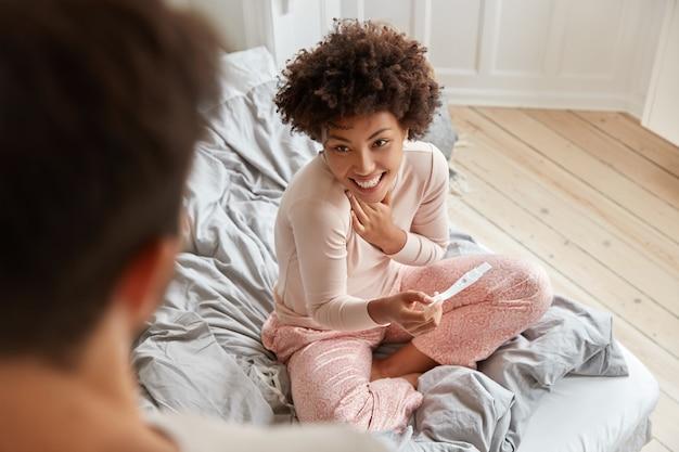 Widok z góry przyszłej matki cheerul czarnej w piżamie