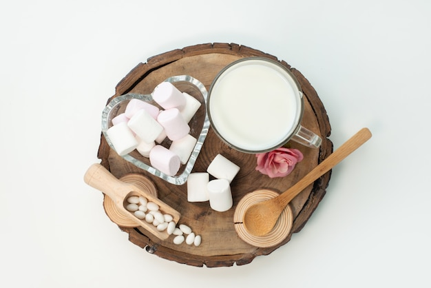 Widok z góry ptasie mleczko i mleko na brązowych drewnianych i białych cukierkach cukrowych