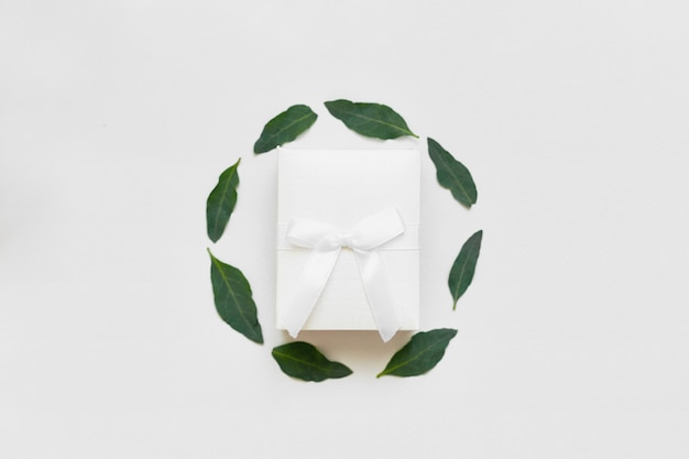 Widok z góry pudełko gist w ramce okrągłe koło zielonych liści. ślub leżał płasko