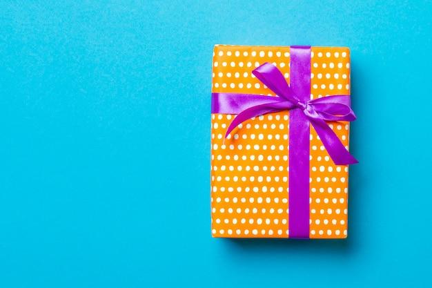Widok z góry pudełko na prezent z fioletową kokardką na niebieskiej powierzchni z miejsca kopiowania