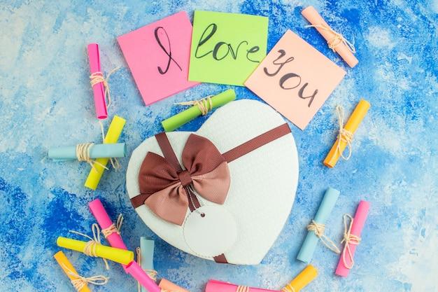 Widok z góry pudełko w kształcie serca kocham cię napisane na karteczkach samoprzylepnych przewiń papiery życzeń na niebieskim tle