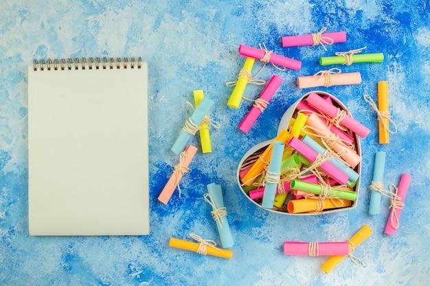 Widok z góry pudełko w kształcie serca z notatnikiem z życzeniami na niebieskim tle