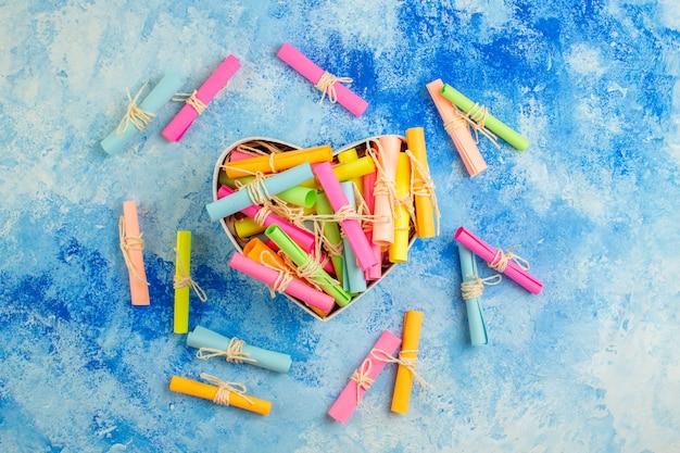 Widok z góry pudełko w kształcie serca z przewijanymi papierami życzeń na niebieskim tle tock photo