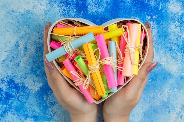Widok z góry pudełko w kształcie serca z przewijanymi papierami życzeń w rękach kobiety na niebieskim tle