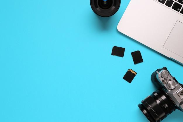 Widok z góry pulpitu fotografa składającego się z aparatu, laptopa, notebooka i karty pamięci na niebieskim tle biurka - kopia przestrzeń.
