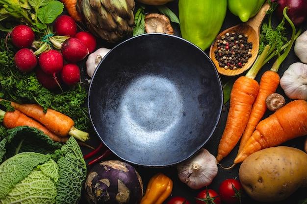 Widok z góry pusta rustykalna miska ceramiczna i świeże warzywa ekologiczne gospodarstwa na rustykalne czarne tło betonu. jesienne zbiory, wegetariańskie jedzenie lub czysta, zdrowa koncepcja odżywiania z miejscem na tekst