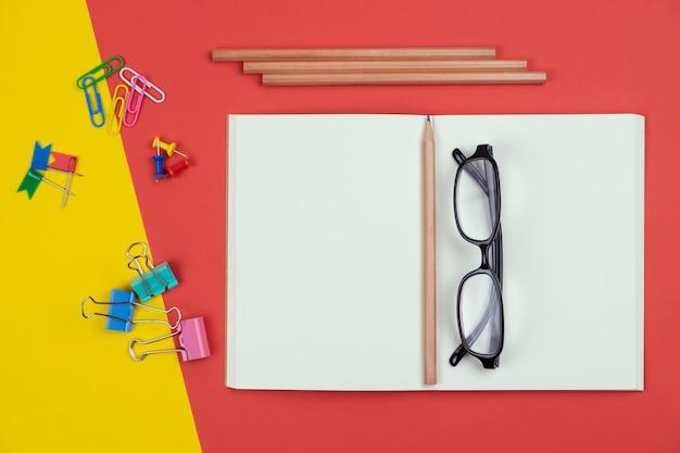 Widok z góry puste otwarty notatnik z ołówkiem i artykuły papiernicze i okulary