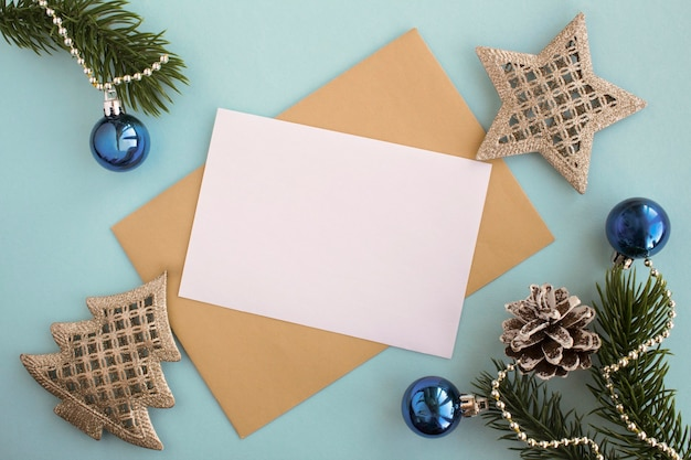 Widok z góry pustego białego papieru dla tekstu, koperty i składu bożego narodzenia na niebieskim tle. skopiuj miejsce.