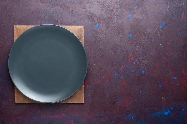 Widok z góry pustego ciemnego okrągłego talerza utworzonego na ciemnej powierzchni